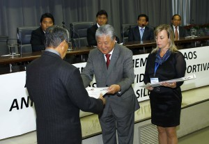 O vereador Ushitaro Kamia entrega os diplomas aos associados da ACET